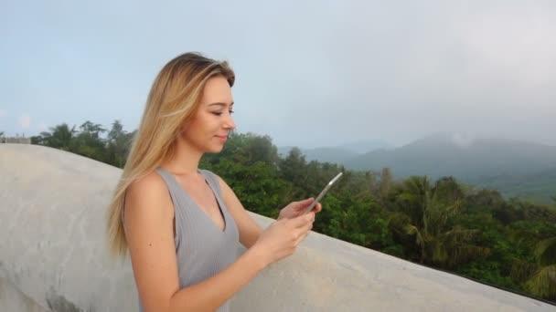 Slow motion fashion designer girl using tablet looking at breathtaking landscape.