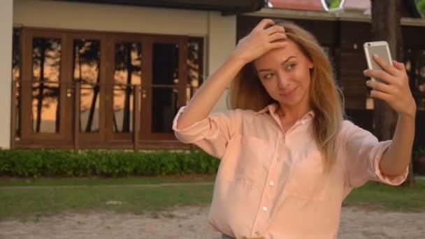 Slow motion fashion designer female taking selfies on smartphone near mansion