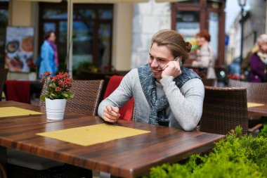 Young caucasian man sitting at sreet cafe and talking by smartphone.