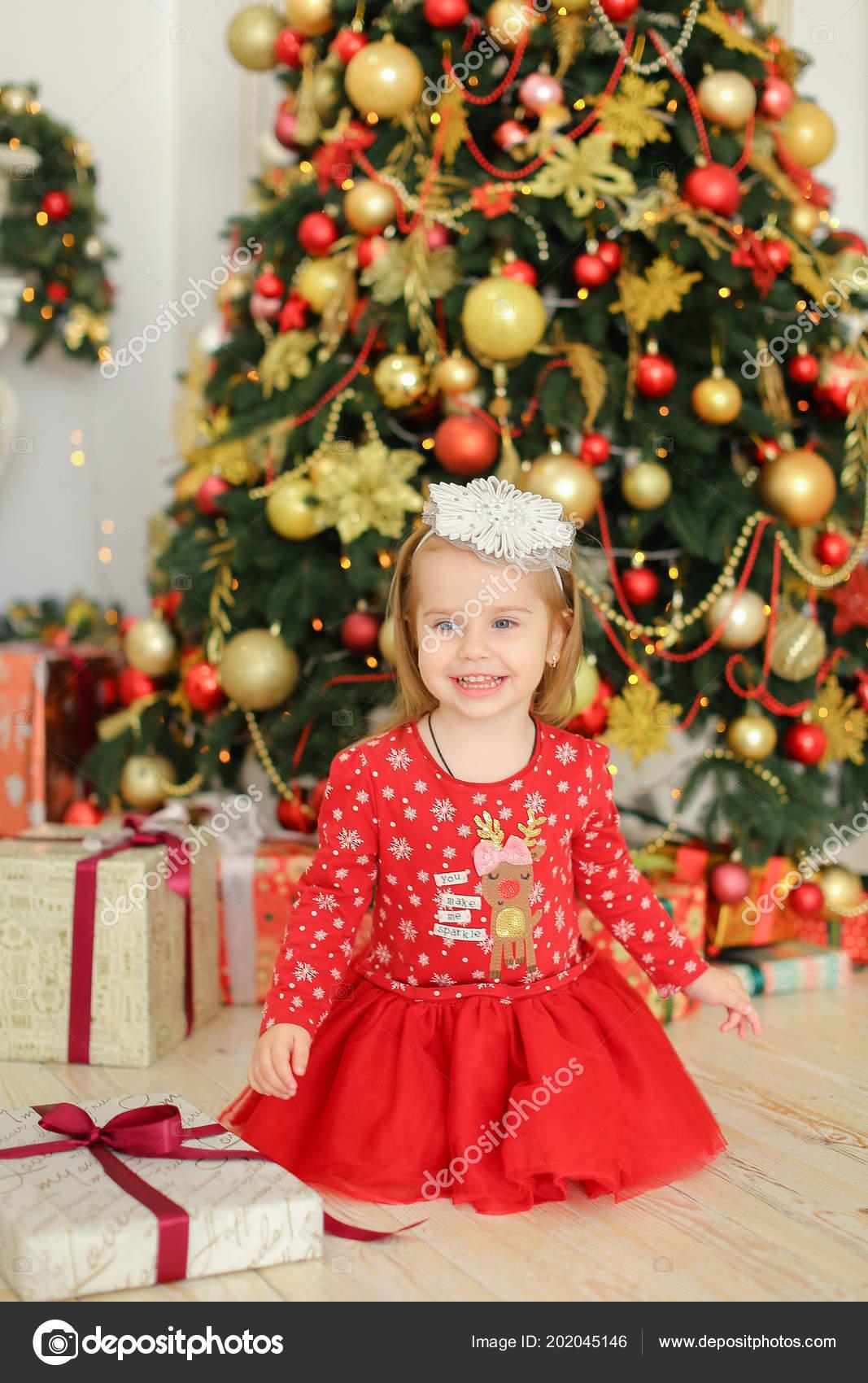 fe494ee991 Sonriente mujer niño vestido rojo sentado en el piso cerca de regalos y el  árbol de Navidad. Concepto de invierno días de fiesta inspiración y  presenta ...