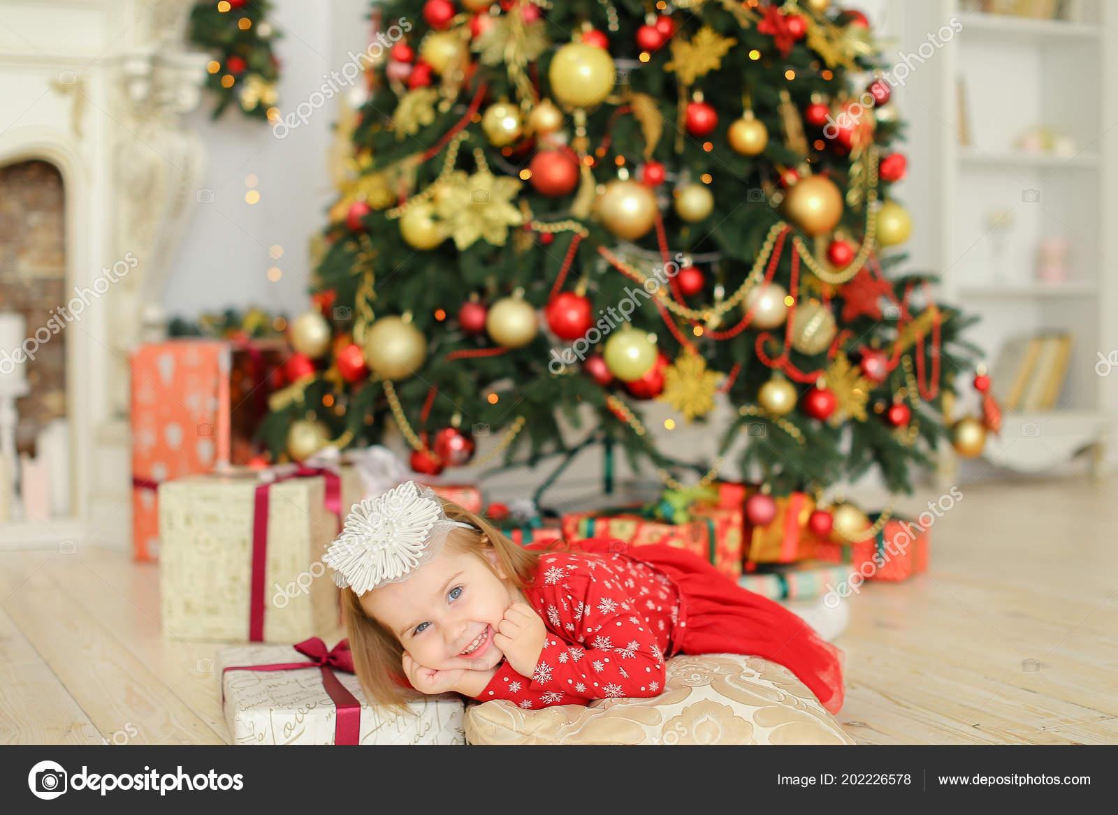 17924fab97 Caucásica niña con vestido rojo de mentira cerca de árbol de Navidad y  regalos. Concepto de la celebración de vacaciones de invierno
