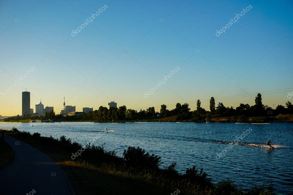 Wakesurfing on Danube river with sunset background and view on Vienna.