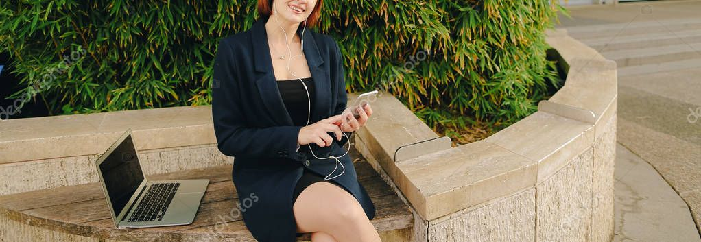 Secretary listening to music with in ear phones and smartphone o