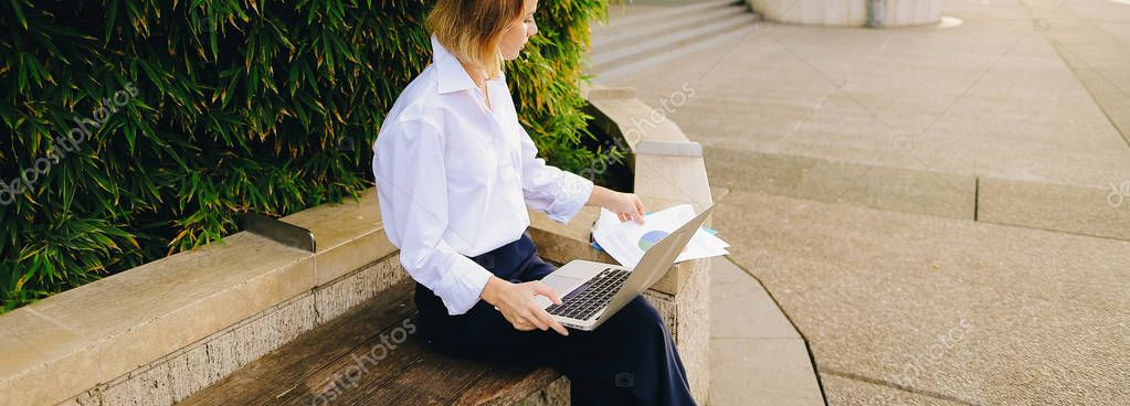 Close up face of woman typing with laptop outdoors.