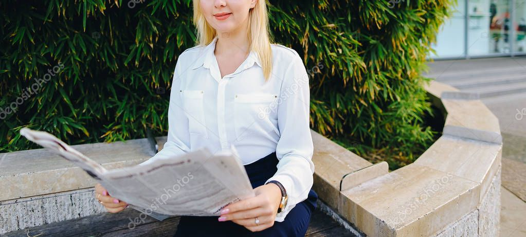 Lady reading newspaper outdoors in   with close up face.