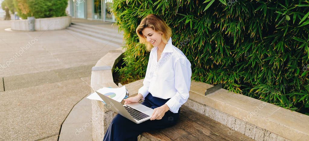 Statistician working outside with laptop and color diagrams.