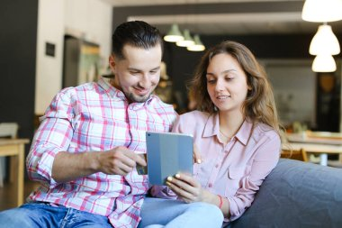 Young american man and woman using tablet at cafe with debit card.