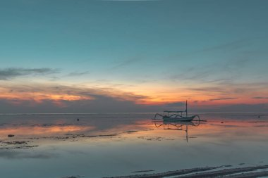 Indonesian fishing boat with outriggers at twilight time, close to the shore, red reflections in the water, Sanur, Bali, Indonesia, April 21, 2018
