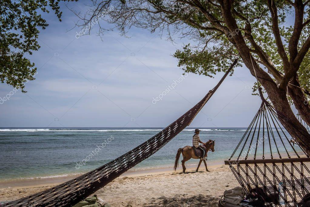 Black hammocks on the beach and a horse rider comes along the shore,  Gili  Trawngan, Indonesia, April 25, 2018