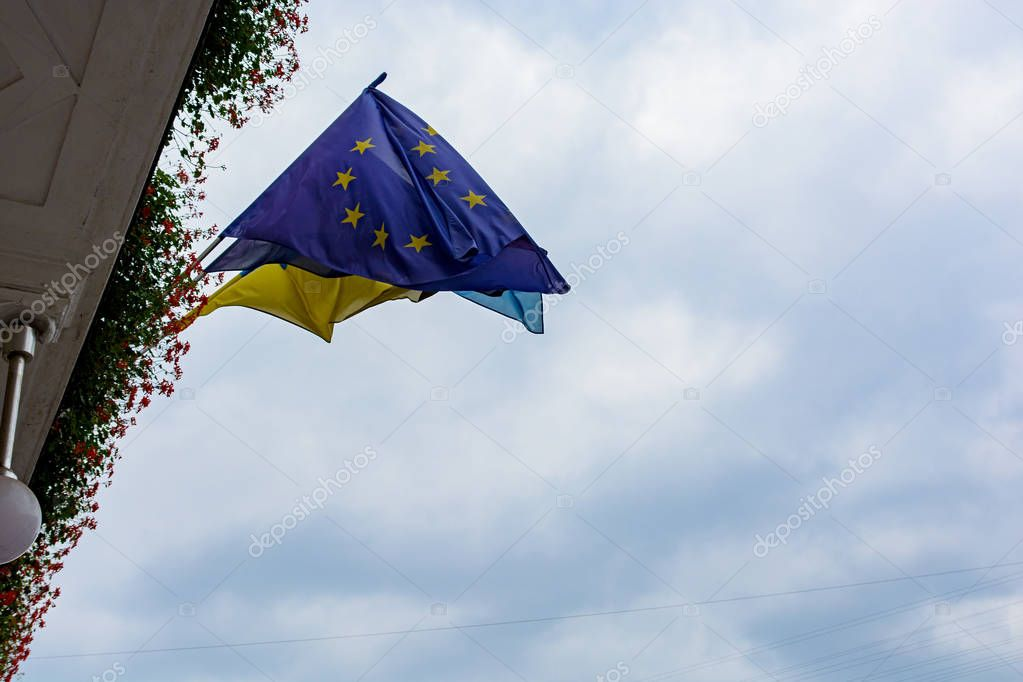 European and Ukrainian flag on the background of sky and clouds.