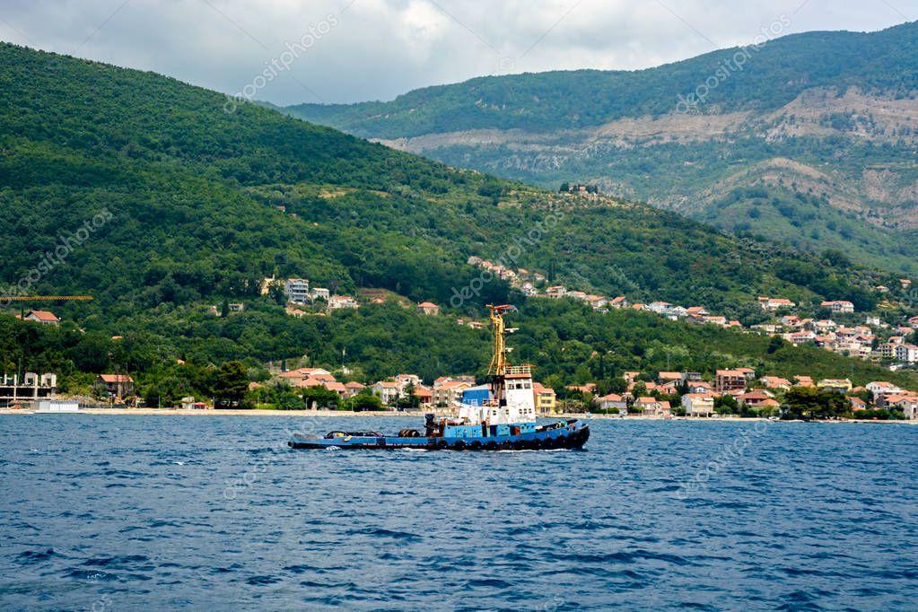 The marine tugboat sails along the coastline