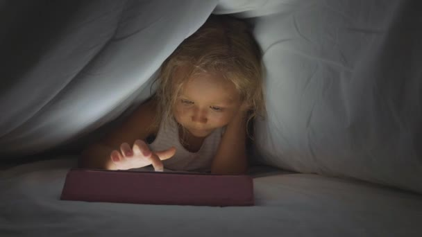 Little cute girl lying under duvet and using digital tablet device at bedtime.