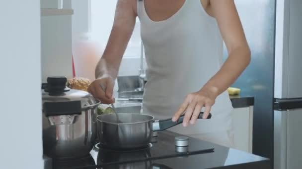 Junge Hausfrau Kochen Abendessen, tanzen und reden mit dem Handy