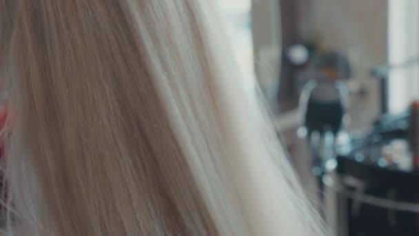 Česání vlasy na blond dívka v salonu krásy, mužský kadeřník detail