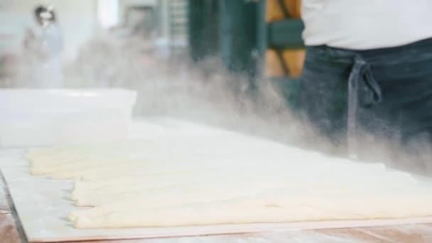 Professioneller Bäcker Gießen eine Mehl auf raw Brot vor dem Backen in der Bäckerei Küche