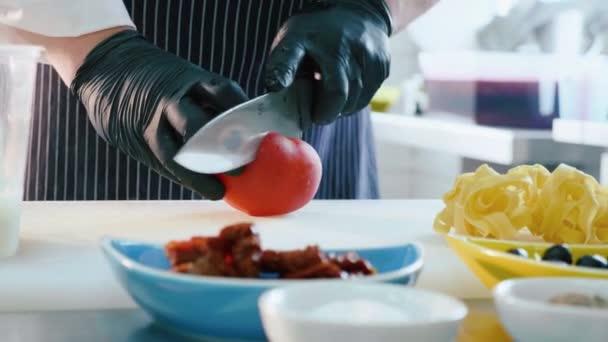 Chef cutting tomato for preparing italian food