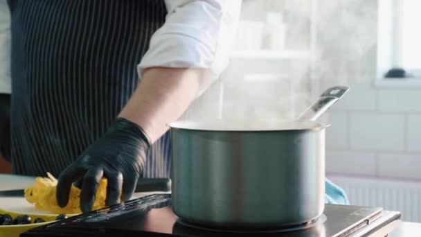 Close-up of chef puts a pasta in a steaming saucepan on a stove