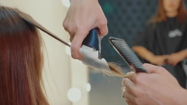 Woman getting polishing hair by hairdresser at beauty salon, close-up