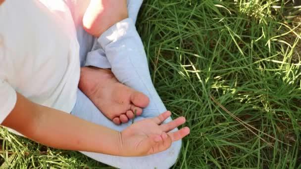 kleines süßes Mädchen meditiert auf dem Rasen im grünen Sommerpark.