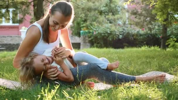 Happy family of young sporty mother and little cute daughter having fun outdoors