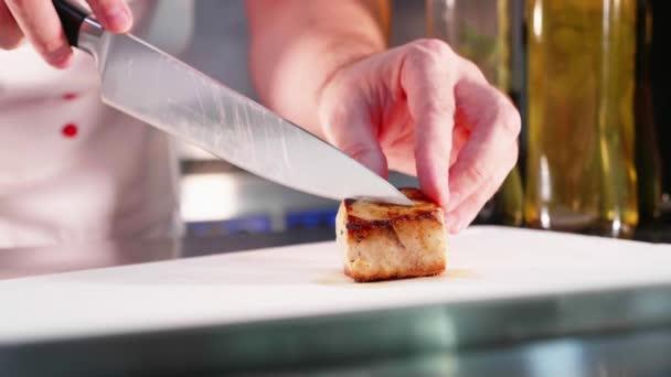 Kuchař je obloha filet tuňáka v kuchyni Restaurace v pomalém pohybu