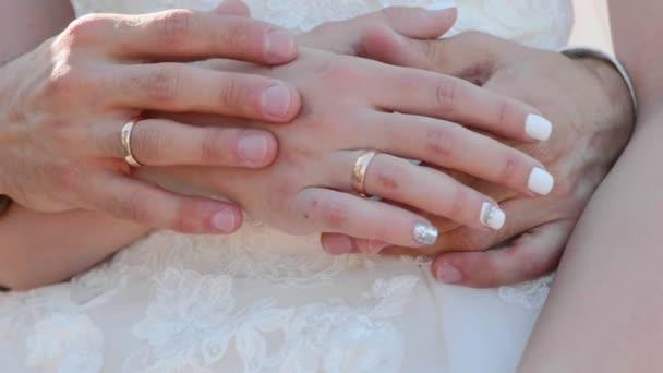 Közelről az ifjú kezét gyűrűk finoman érintkeznek egymással.
