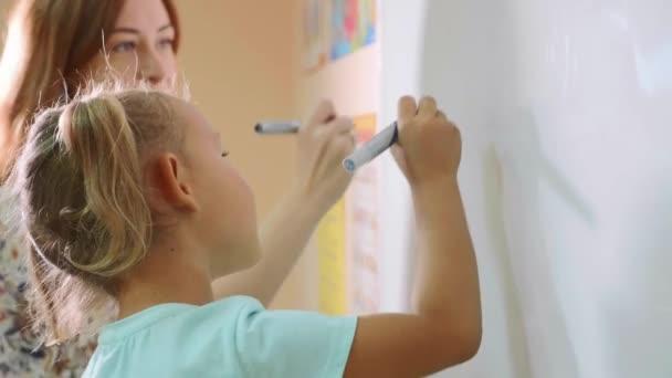 Malá roztomilá holčička s učitelem psaní na tabuli ve třídě