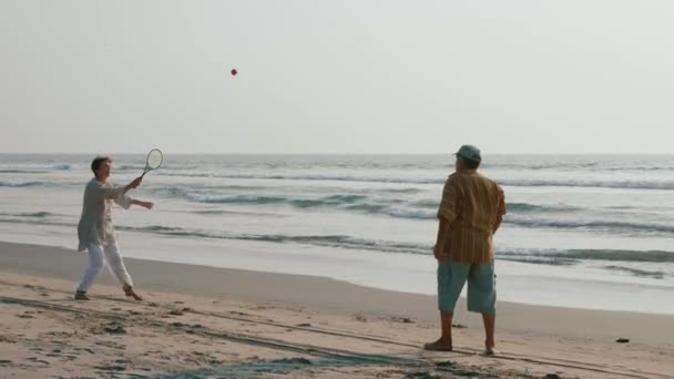 Active senior couple playing tai chi ballon ball at the beach.