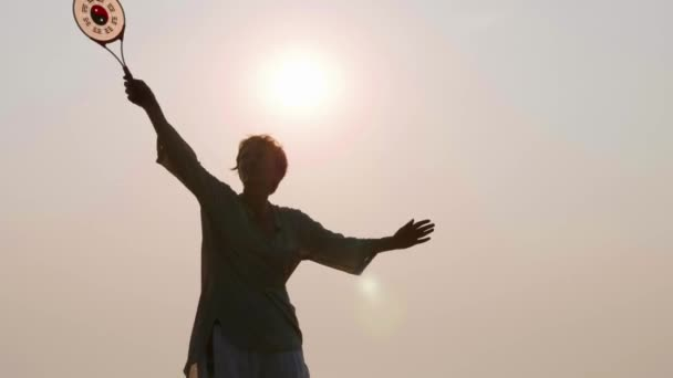 Seniorin übt Tai Chi Ballon Ball am Strand bei Sonnenuntergang