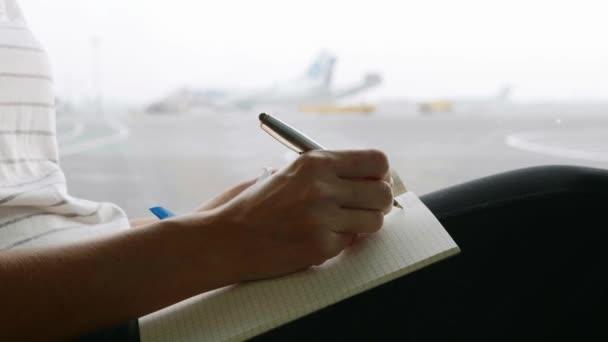 Mladá žena, psaní deníku na letišti, detail
