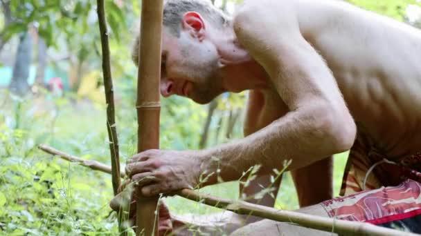 Kavkazské muži pomocí bambusové dřevo pro budování přírodní plot na zahradě