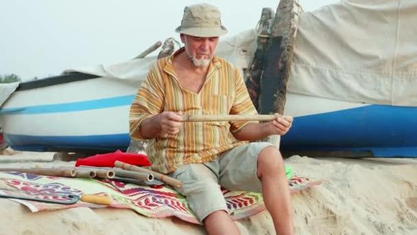 Starší muž sedí a výběru bambus škrty za dílo flétna