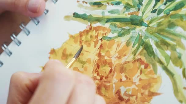 Close-up of female hand with paintbrush is drawing pineapple in sketchbook by watercolors