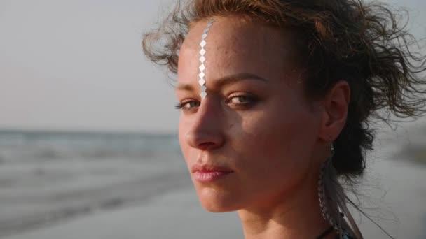 Porträt einer jungen hübschen Frau, die aufs Meer blickt und sich dann der Kamera zuwendet