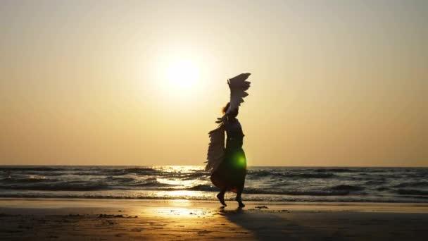 Sziluettjét fiatal lány angyal szárnyakkal, napnyugtakor a lassú tánc