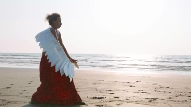 Young girl with angel wings dancing at sunset