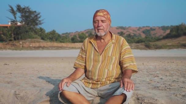 Starší muž sedí a přemýšlí na písečné pláži