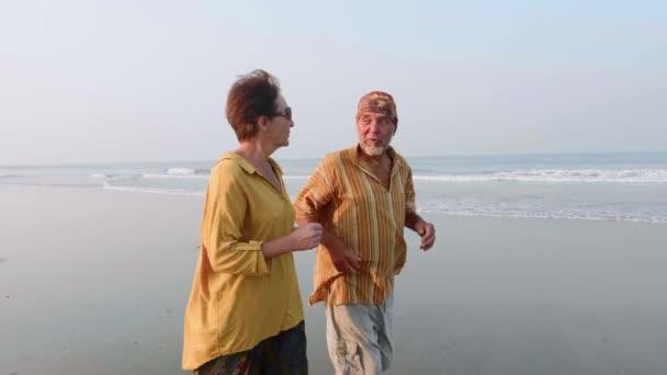 Active senior couple running on the sandy beach at sunrise