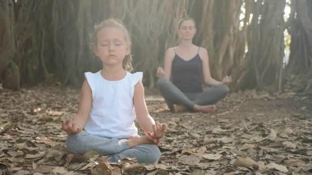 kleines Mädchen mit junger Mutter beim gemeinsamen Meditieren unter einem Banyan-Baum