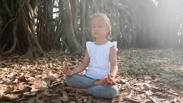 kleines Mädchen meditiert allein unter einem Banyan-Baum