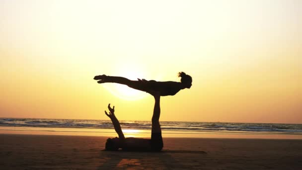 Fit sporty couple practicing acro yoga with partner together on the sandy beach.