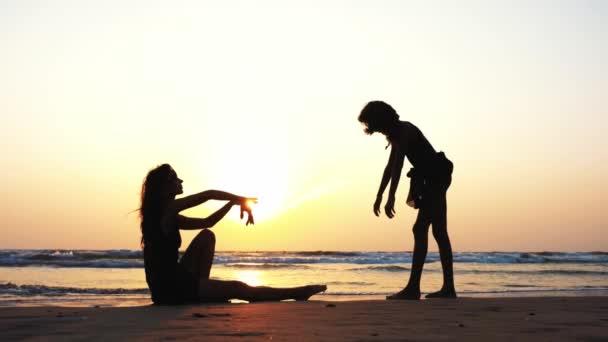 Sziluettjét egy nő vonatok egy lány, hogy végre akrobatikus elem, a strandon.