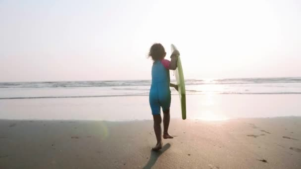 Little girl is running on the sea to waves holding surfboard in her hands.
