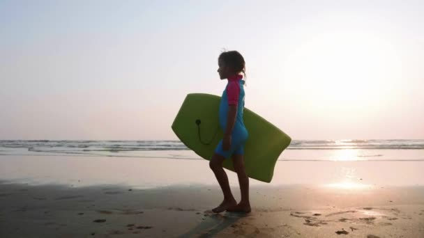 Little girl is walking along the ocean sand beach with surfboard at sunset.
