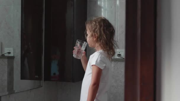 Little curly child girl rinses her mouth with water in bathroom, side view.