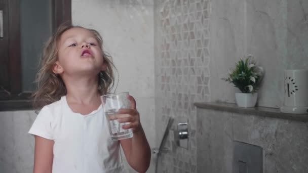 Little curly child girl rinses her mouth with water.