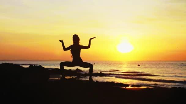 Mladé ženy silueta dělá jóga cvičení na pláži oceánu při západu slunce.