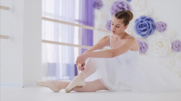 Graceful young ballerina in white tutu ties pointes sitting on the floor.