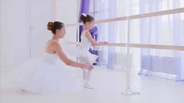 Ballet teacher in white tutu is training little girl near the barre stand.