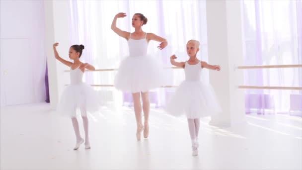 Balett-tanár gyerekekkel Tutus táncolnak lábujjhegyen a pointes az osztályban.